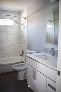 The newly refreshed bathroom features white subway tile and matching cabinets